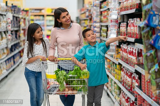 Beautiful latin american single parent with her two kids at the supermarket shopping for groceries and boy pointing at something both smiling