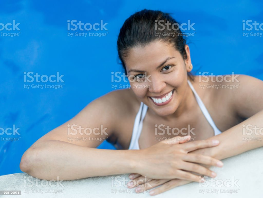 Beautiful latin american woman leaning her arms at the edge of the...