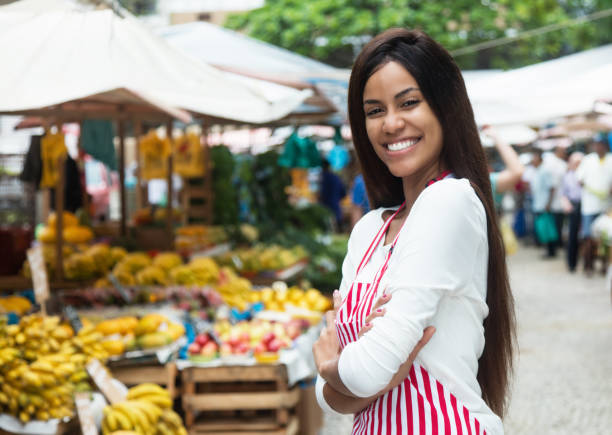 Beautiful latin american woman selling fruits at farmers market Beautiful latin american woman selling fruits outdoors at farmers market central america stock pictures, royalty-free photos & images