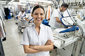 Beautiful latin american young supervisor at an industrial laundry service smiling at camera with arms crossed - Incidental people working at background