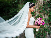 Beautiful latin bride with long veil and bouquet
