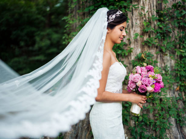 Beautiful latin bride with long veil and bouquet stock photo
