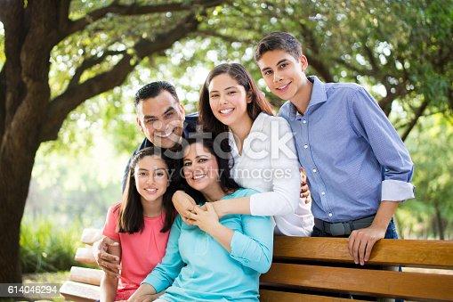 istock Beautiful latin family smiling at the camera outdoors 614046294