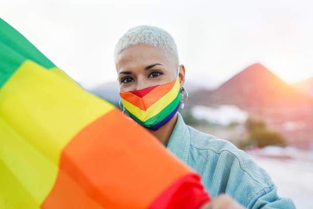 lgbtプライド虹の旗屋外で美しいラテンレズビアンの女性 - lgbtqi  ストックフォトと画像