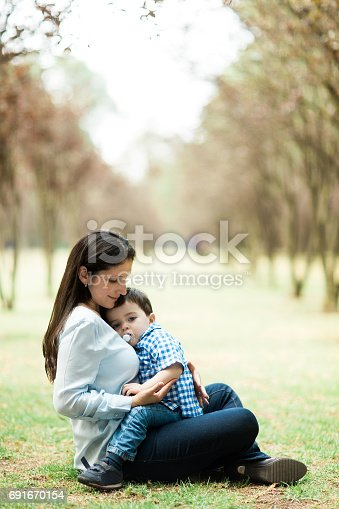 811227514 istock photo Beautiful latin mother and child sitting on grass 691670154