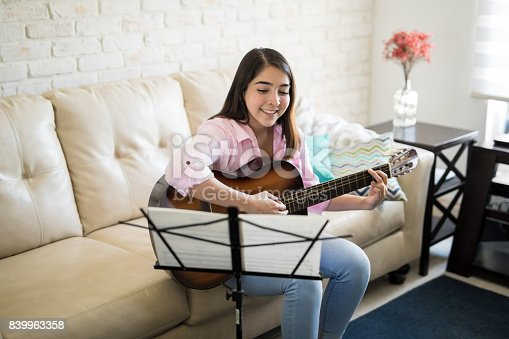 istock Beautiful Latin singing and playing the guitar 839963358