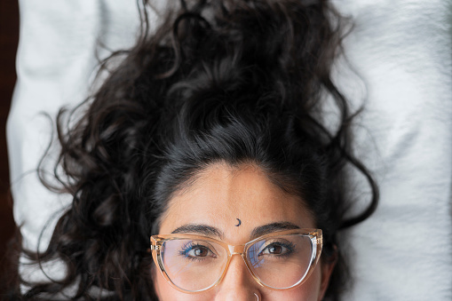 Beautiful Latin woman from Bogotá Colombia between 30 and 34 years old, lying down looking at the camera wearing her glasses and disheveled