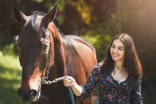 schöne lateinische frau in kleid und ihre schöne pferd zu fuß im wald. liebe tiere konzept. liebe pferde - pferdezeitschrift stock-fotos und bilder