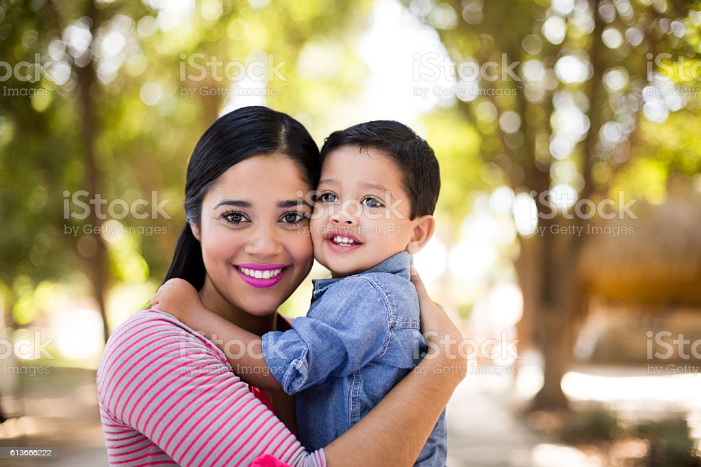 Beautiful latin young mother and son smiling at camera stock photo