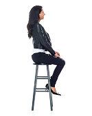 Beautiful Latino female wearing a leather jacket - sitting