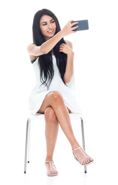 Beautiful latino female wearing a white dress while sitting and is taking a selfie stock photo