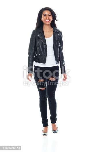 Beautiful Latino female wearing leather jacket and torn jeans - walking