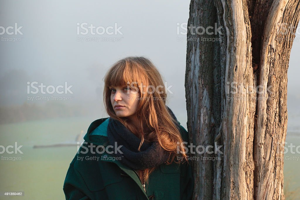 Foggy autumn Latvian outdoor girl model leaning against tree stock photo