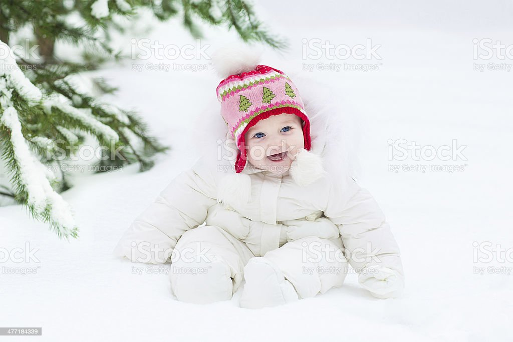 Beautiful laughing baby girl sitting under Christmas tree royalty-free stock photo