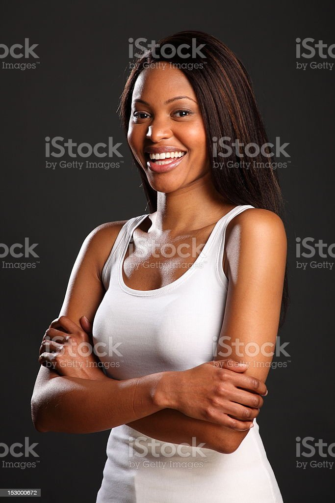 Beautiful laughing black woman in white vest with arms folded stock photo