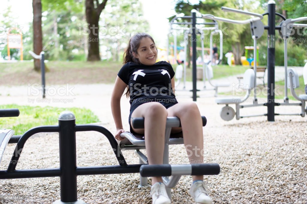 A beautiful, laughing girl doing exercises outside. - Royalty-free Adult Stock Photo