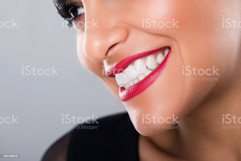 Beautiful laughing woman with red lips and white teeth, closeup stock photo