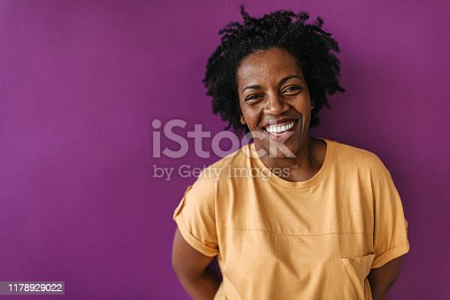 Afro woman laughing in front of purple wall at studio, looking at camera