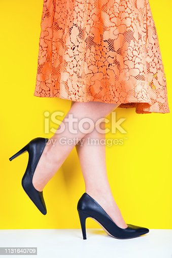 Beautiful legs of young woman in colorful skirt and black shoes with high heels on vibrant yellow background. Studio shot with copy space.