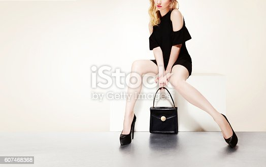 istock Beautiful legs with black heels and handbag purse woman sitting. 607468368