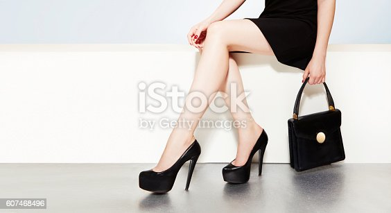 istock Beautiful legs with black heels and handbag purse woman witting. 607468496