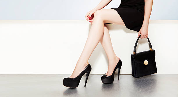 Beautiful legs with black heels and handbag purse woman witting. - foto de stock