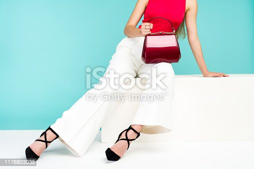 istock Beautiful legs woman sitting on the bench. With red purse and high heel shoes. 1176803035