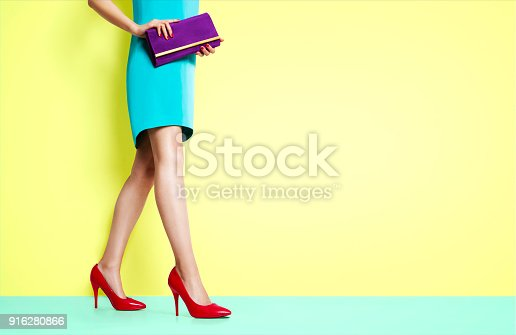 istock Beautiful legs woman walking with red heels shoes. 916280866