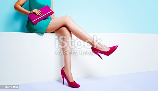 istock Beautiful legs woman wearing blue dress with a purple purse hand bag with red high heels shoes sitting on the white bench. with copyspace. 916280864