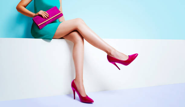 Beautiful legs woman wearing blue dress with a purple purse hand bag with red high heels shoes sitting on the white bench. with copyspace. stock photo