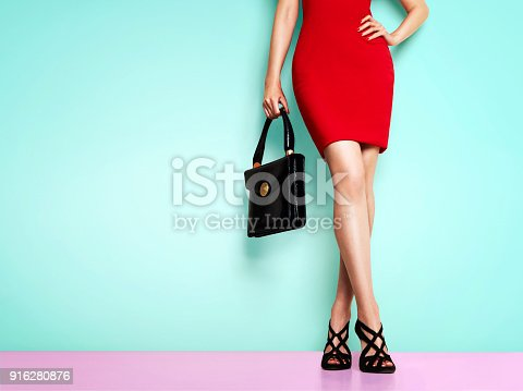 539468216 istock photo Beautiful legs woman wearing red dress, black shoes and handbag standing against light blue wall. isolated. Business woman fashion image. 916280876