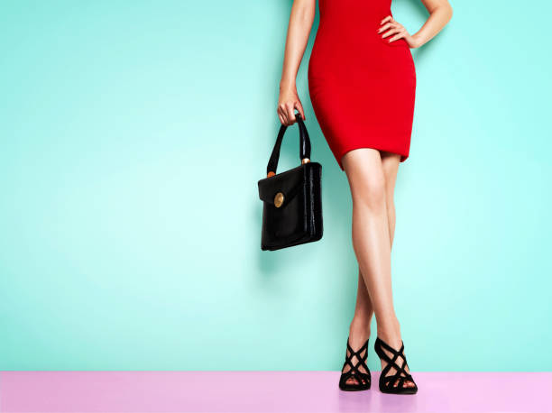 Beautiful legs woman wearing red dress, black shoes and handbag standing against light blue wall. isolated. Business woman fashion image. stock photo