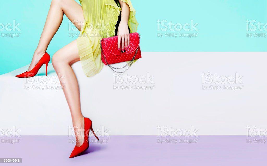 Beautiful legs woman with red shoes and purse sitting on the stairs.Isolated on light blue background. stock photo