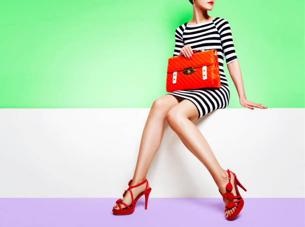 Beautiful legs woman with red shoes with orange bag sitting on the white bench Woman wearing stripe dress, red elegant sandals heels, holding an orange purse bag sitting with the colourful green background. fashion stock pictures, royalty-free photos & images
