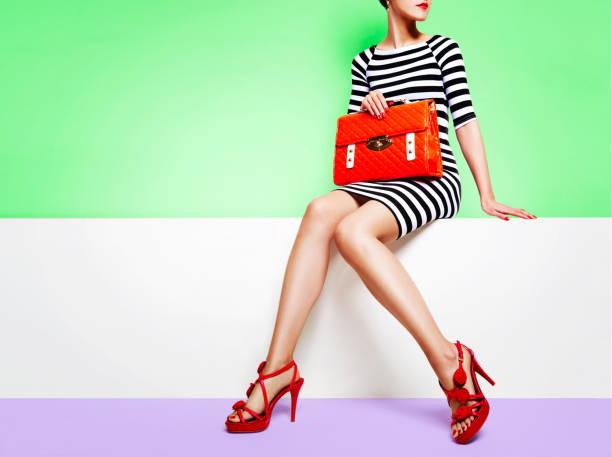 오렌지 가방 화이트 벤치에 앉아 빨간 구두와 함께 아름 다운 다리 여자 - 우아 뉴스 사진 이미지