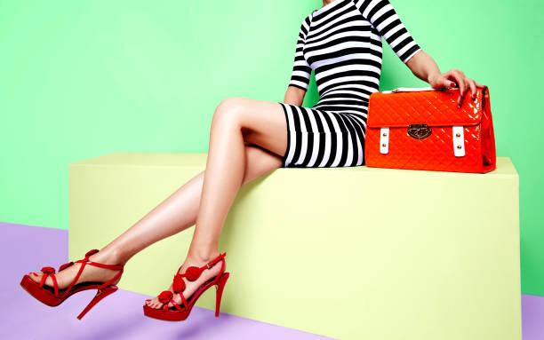 schöne beine frau mit roten schuhen mit orange tasche auf der gelben bank sitzen - lange gestreifte röcke stock-fotos und bilder