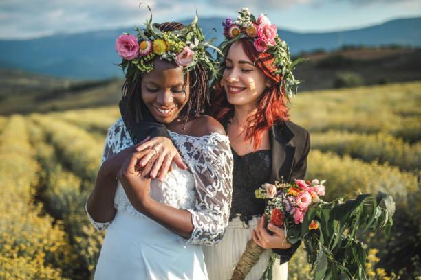 Beautiful lesbian boho brides embracing in nature stock photo
