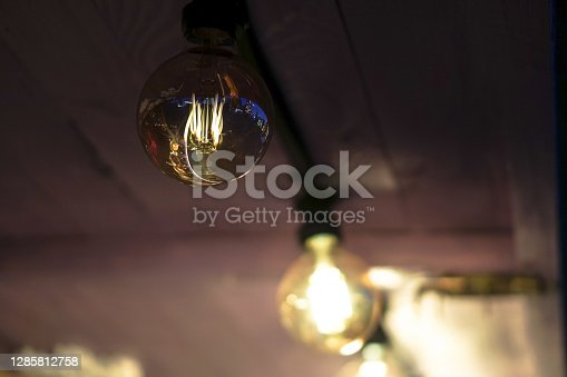 Beautiful light bulb shines in the dark. electric light at night.
