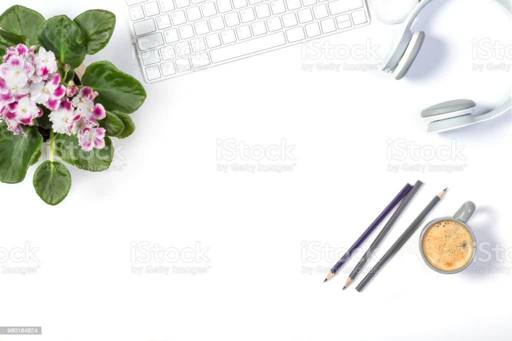 Beautiful light mockup. White modern keyboard, headphones, color pencils, lovely flower pot and small gray cup of coffee on white background. Enjoying little things. Top view. stock photo