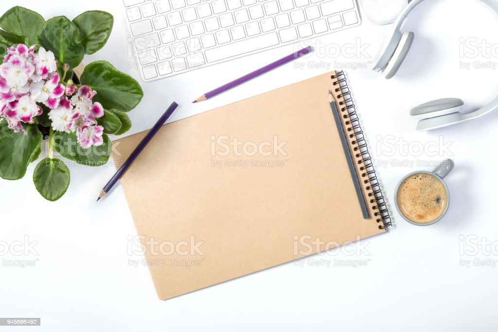 Beautiful light mockup. White modern keyboard, headphones, stationery, lovely flower pot and small gray cup of coffee on white background. Enjoying little things. Top view. stock photo
