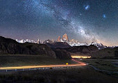 Beautiful light trails towards remote town El Chalten - Fitz Roy Mountain visible under Milky Way