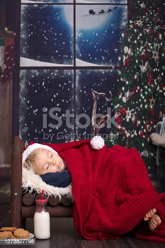Beautiful little baby boy, sleeping in small wooden bed, waiting for Santa Claus to come and bring presents, cookies and milk prepared