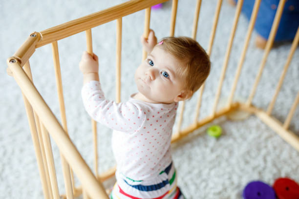 beautiful little baby girl standing inside playpen. cute adorable child playing with colorful toys. home or nursery, safety for kids. alone baby waiting for mom - playpen stock pictures, royalty-free photos & images