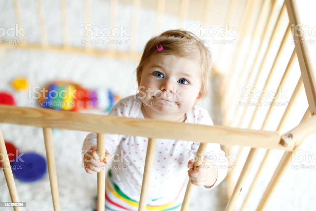 Beautiful little baby girl standing inside playpen. Cute adorable child playing with colorful toy stock photo