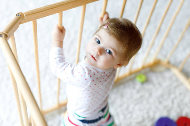 beautiful little baby girl standing inside playpen. cute adorable child playing with colorful toy - playpen stock pictures, royalty-free photos & images