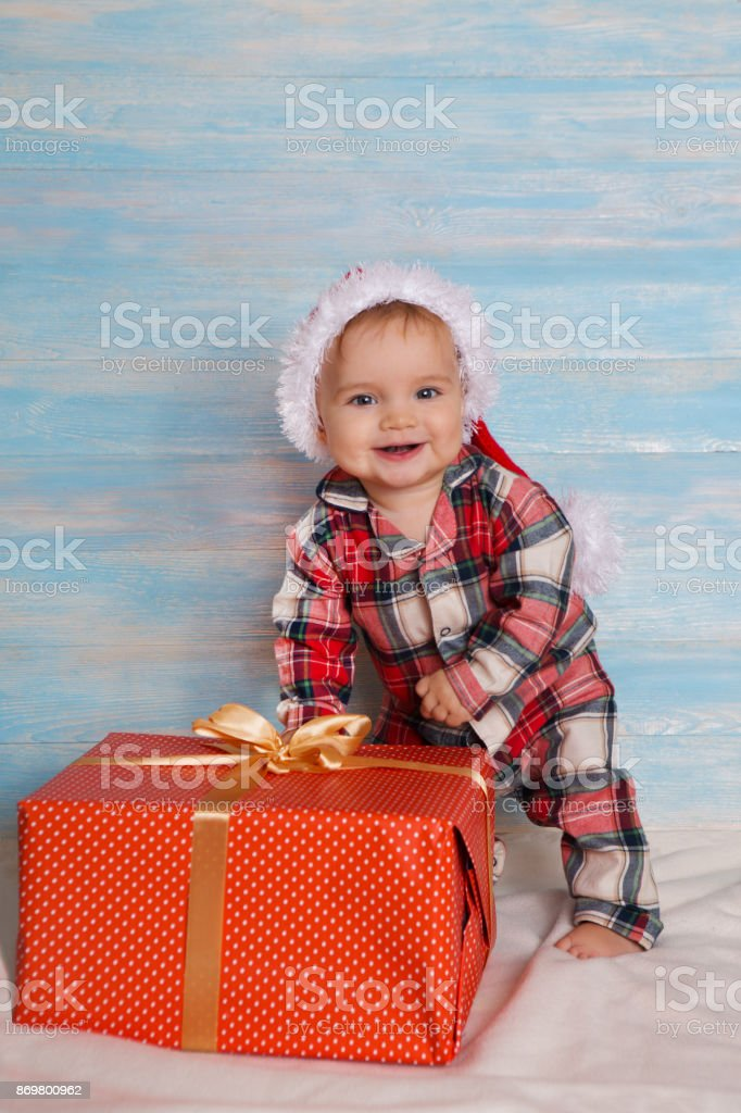 beautiful little baby with gift celebrates Christmas. New Year\'s...