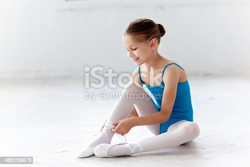 istock Beautiful little ballerina in blue dress for dancing puting on 483256678