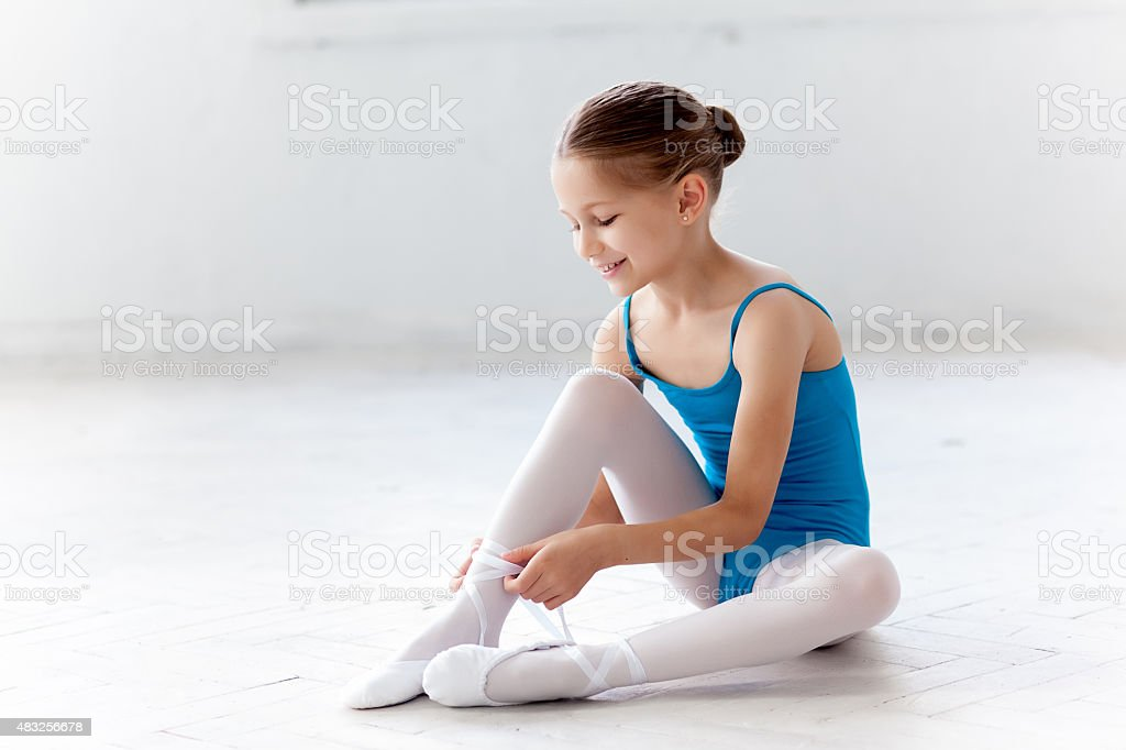 Beautiful little ballerina in blue dress for dancing puting on stock photo