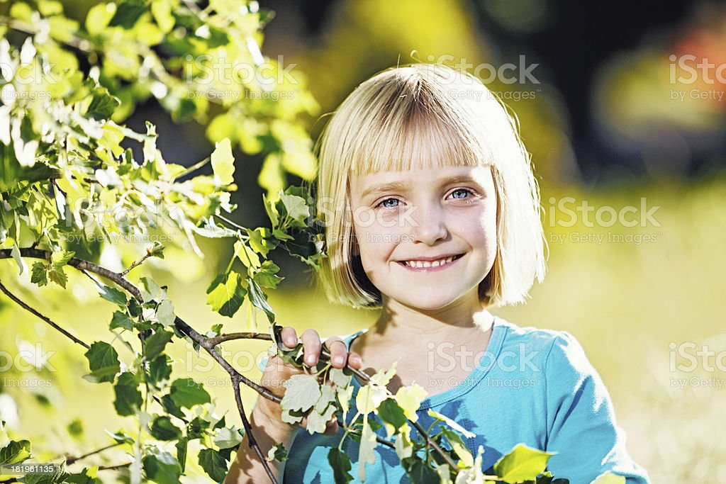 Beautiful little blonde girl smiling by springtime tree stock photo