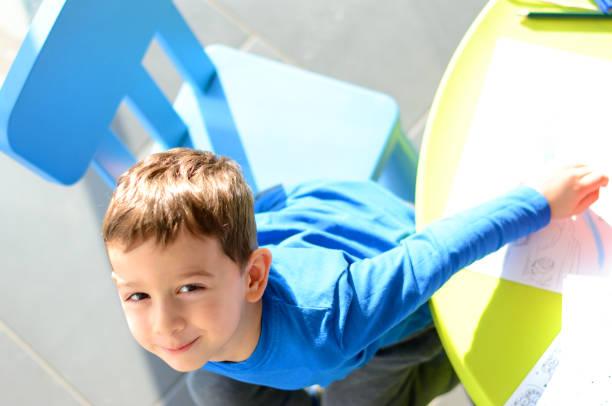 schöne kleine junge im spielzimmer spielen. ansicht von oben - knete spiele stock-fotos und bilder